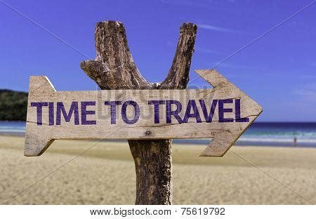 Time to Travel wooden sign with a beach on background