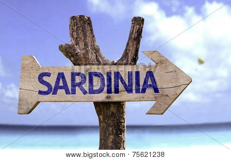 Sardinia wooden sign with a beach on background