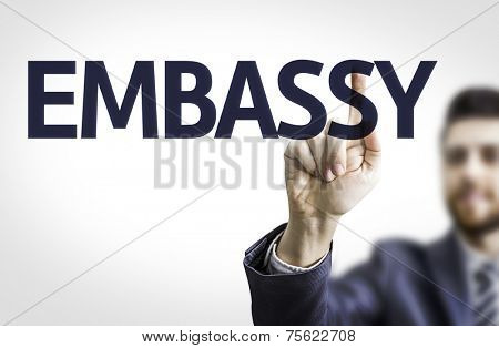 Business man pointing to transparent board with text: Embassy