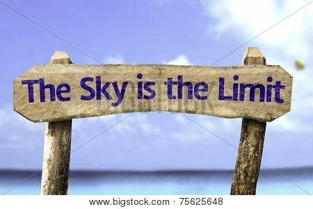 The Sky is The Limit wooden sign with a beach on background