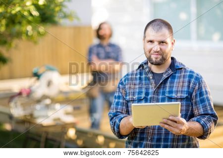 Portrait of mid adult manual worker holding digital tablet with coworker standing in background at construction site