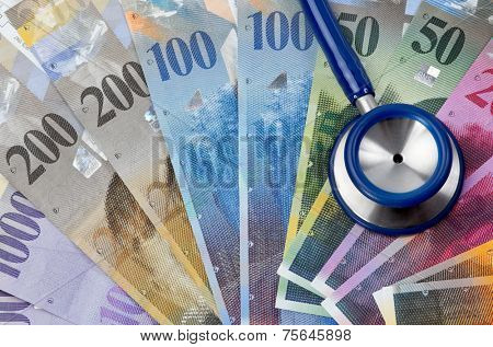 swiss francs and stethoscope. costs for medicine and health.