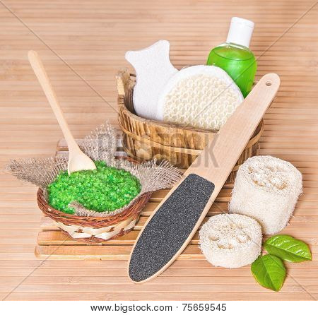Accessories for peeling: shower gel sea salt pumice wisp loofah with green leaves on wooden background poster