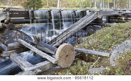 A grindstone connected to water power in an old wooden construction.