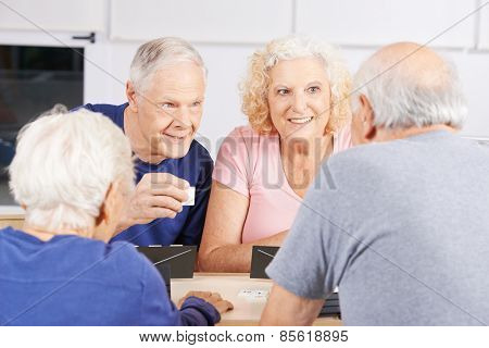 Group of senior people playing rummikub game in a nursing home