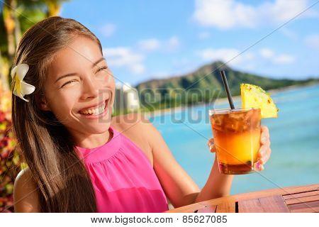 Beach bar party drinking friends toasting Hawaiian sunset cocktails having fun. Asian woman looking at camera holding alcoholic drink cheering in Waikiki beach, Honolulu city, Oahu, Hawaii USA.