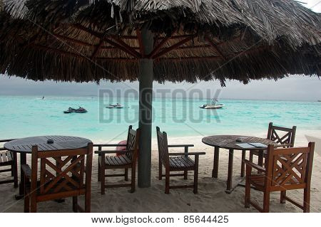 Chairs And Tables Under Big Umbrella At Beach