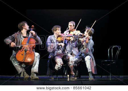 MOSCOW - MAR 12, 2014: Four funny men Taper-show: dancing on the strings in costumes with musical instruments sitting on chairs on stage of the Palace on Yauza