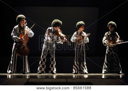 MOSCOW - MAR 12, 2014: Four actors Taper-show: dancing on the strings in black wigs and costumes with musical instruments on stage of the Palace on Yauza