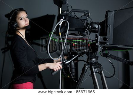 Recording at TV studio.Professional camera operator with headphones and camera in television news
