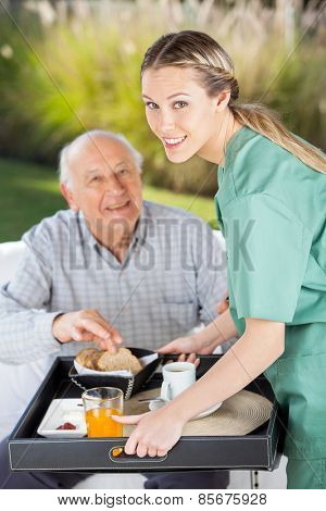 Portrait of smiling female nurse serving breakfast to senior man in nursing home