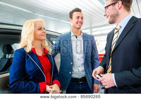 Couple buying car at dealership and consulting salesman