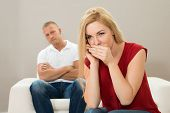Wife Talking Privately On Mobile Phone While Husband Sitting On Sofa poster