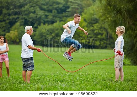 Man rope skipping with jumping rope with his family in nature