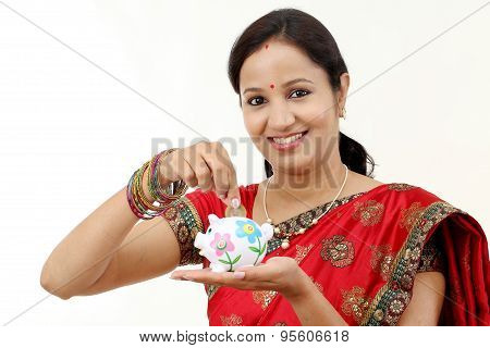 Traditional Indian Woman Holding A Piggy Bank And Rupee Coin-money Saving Concept