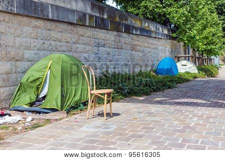 Tents of homeless people at riverside Seine in Paris France poster