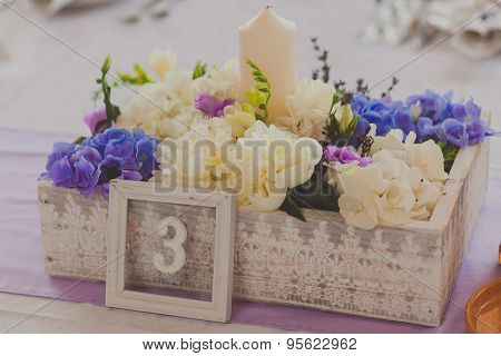 wild flowers in a wooden tub on festive table