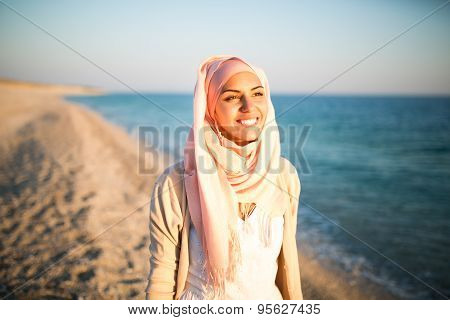 Young beautiful happy muslim woman outdoors portrait.Seaside,beach walk.Beautiful arab saudi woman