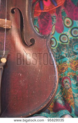 Antique Violin Closeup Against Quirky Fabric Print