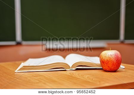 Open Book And An Apple On The Desk In The Classroom. School.