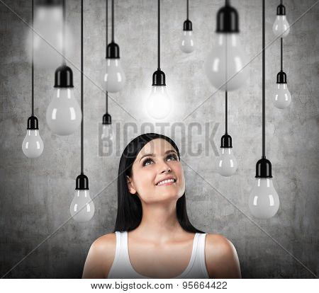 A Dreamy Brunette Looks Upward. Lots Of Light Bulbs, One Of Them Is Turned On. Concrete Background.