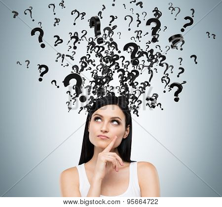 A Portrait Of A Beautiful Brunette With Questioning Expression And Question Marks Above Her Head.