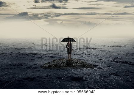 Woman With Umbrella Standing On The Rock In The Middle Of The Sea