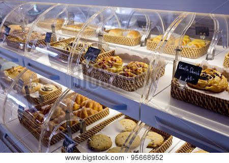 Variety Of Baked Products In Baskets With Bread Name And Price On Black Small Sign Board At A Bakery