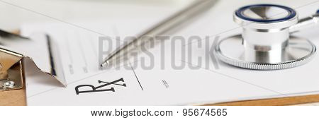 Prescription Form Clipped To Pad Lying On Table With Stethoscope And Silver Pen