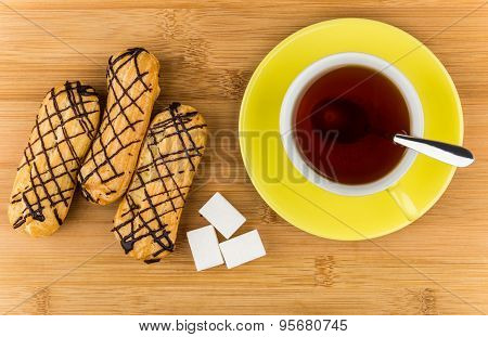 Eclairs, Black Tea In Cup And Lumpy Sugar On Table