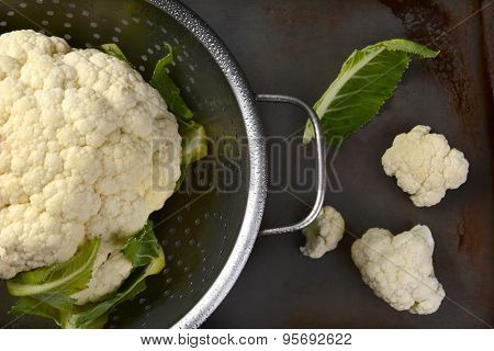 High angle closeup of a colander with a head of cauliflower. On the surface outside are a couple florets and a leaf.