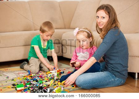 family plays on a flor in living room