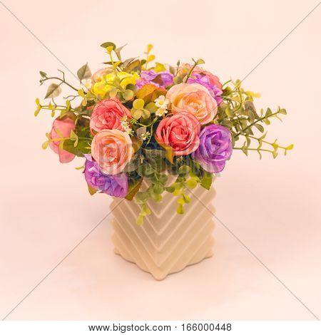 Vintage artificial rose flower in vase on white background