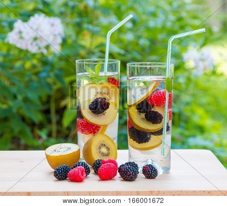 Two glasses of delicious refreshing drink. Infused water with berries golden kiwi and mint. Top view