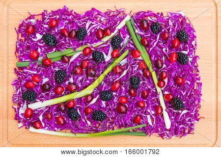 Chopped red cabbage and berries for colorful food background.
