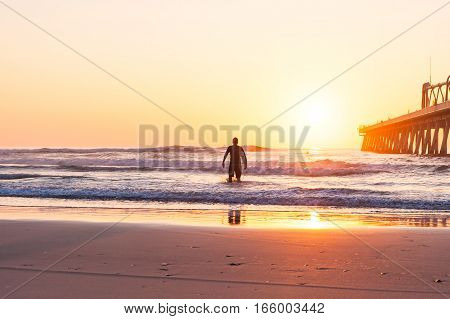 The silhouette of a surfer going for a surf at sunrise