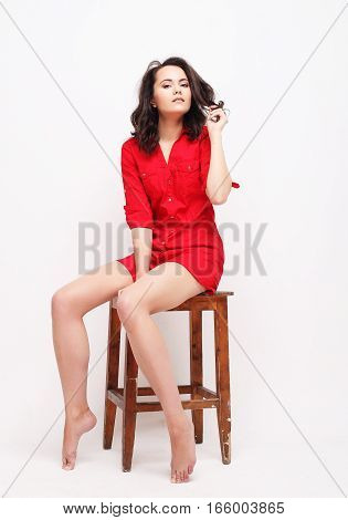 girl in red dress sitting on a stool