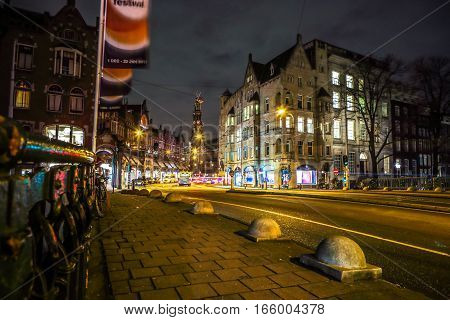 AMSTERDAM NETHERLANDS - JANUARY 09 2017: Amsterdam city night streets with different kinds moving transport & silhouettes of passersby. January 09 2017 in Amsterdam - Netherland.