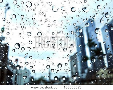 Rain drops cling to a car window glass with skycrapers on the background