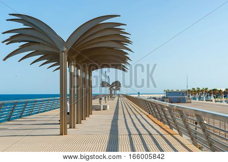 ALICANTE, SPAIN - SEPTEMBER 8, 2016; Sculptural palm trees on elevated pedestrian walkway above breakwater Alicante Spain