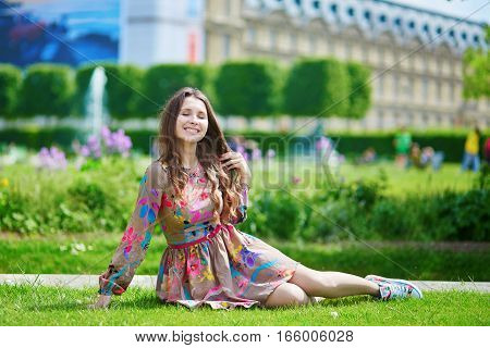 Parisian Woman In The Tuileries Garden Sitting On The Grass