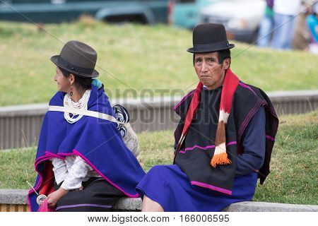 September 6 2016 Silvia Colombia: an indigenous man and woman in traditional wear sitting outdoors on market day