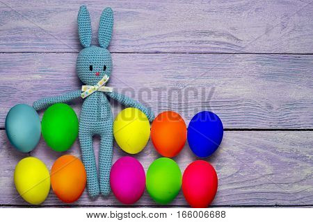 Amigurumi toy easter bunny with colorful eggs on a wooden table - easter background with copy space