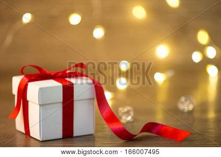 Red gifts tied with a white satin ribbon bow.