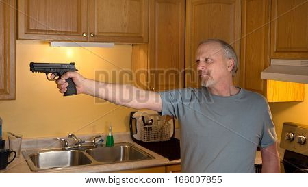 Man with gun in domestic kitchen with serious expression