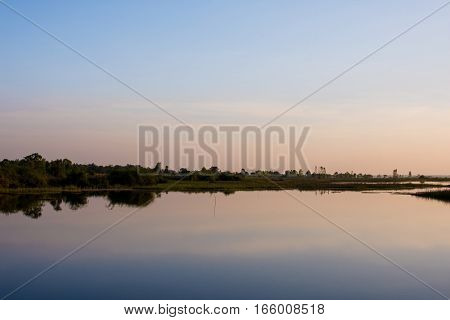 The Sky In Orange And Blue Shades Is Reflected On The Water Of The River.