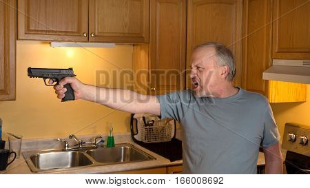 Man with gun in domestic kitchen with angry expression