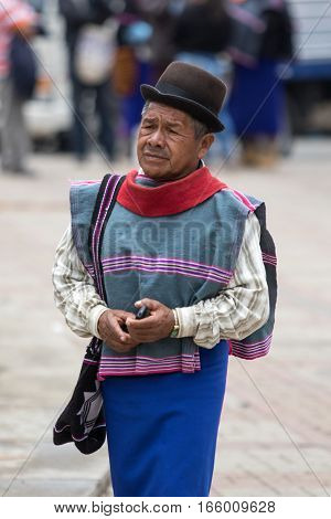 September 6 2016 Silvia Colombia: a Guambiano man wearing traditioal clothing and skirt walks with a cellphone in his hand