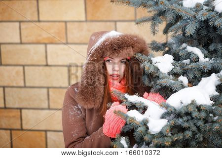 Cute teen girl in pink knitted gloves hats and scarves fur hooded jacket winter walks in the park. She stands next to the Christmas tree. Outdoor Activities. Youth fashion. Close-up portrait