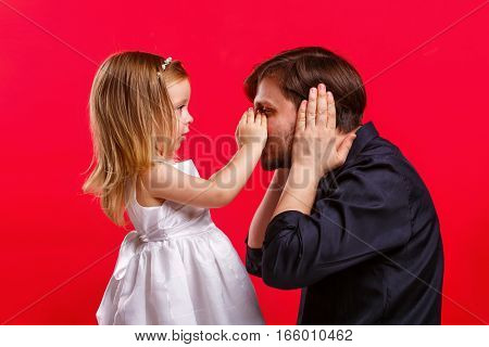 Father and daughter playing. The girl put her hands to his father's nose. He covered his ears. Emotional games with your child. Family fun. The joy of communication. Can not hear anything.